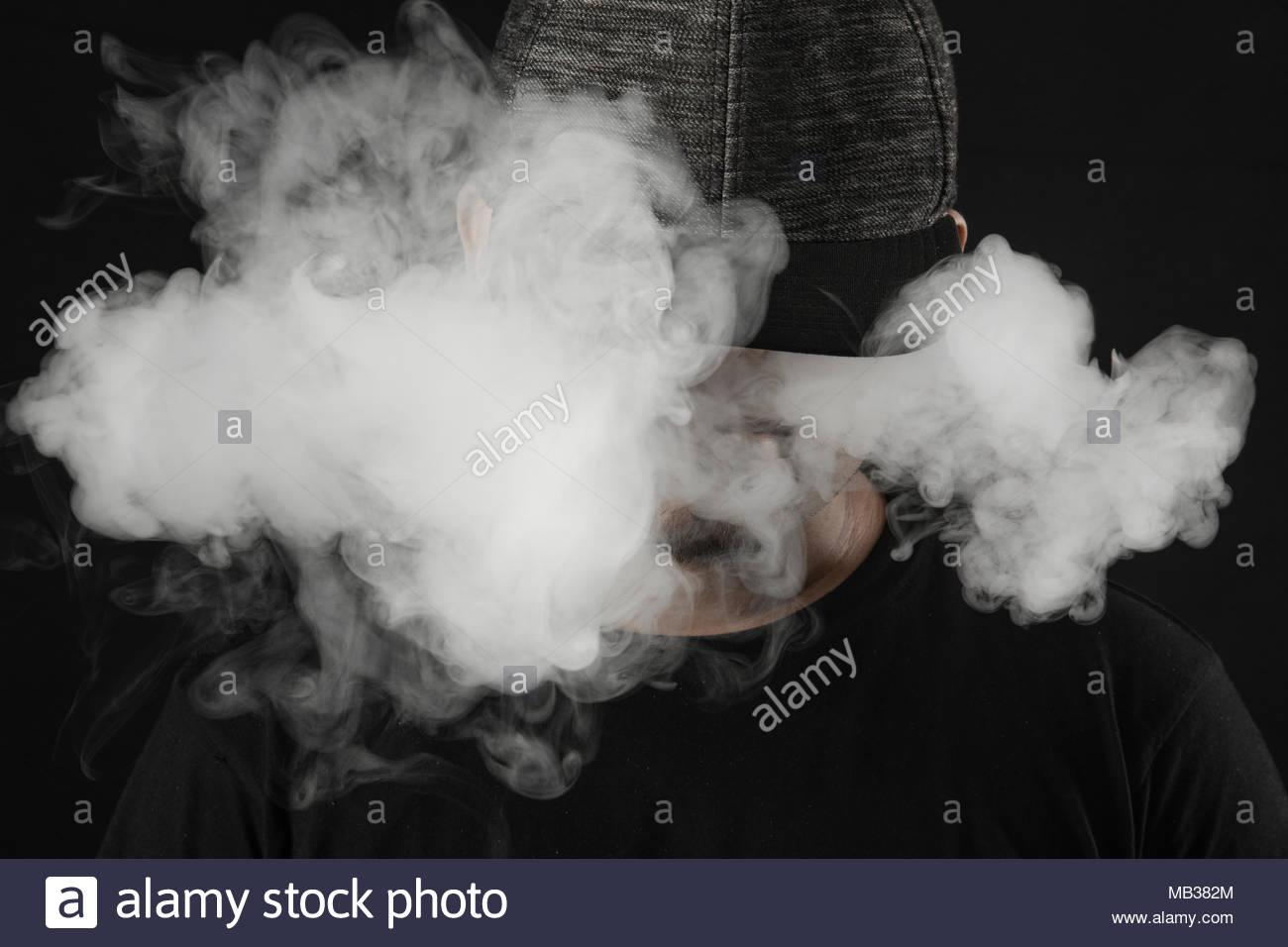 Exhaling smoke/cloud from vaping. - Stock Image