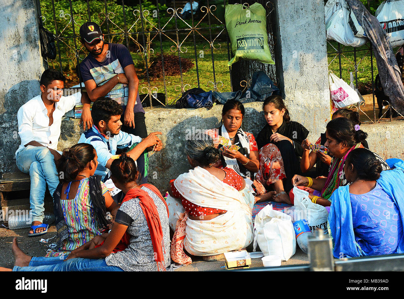 A group of people taking time out to play cards and socialise on a city street, Mumbai, India - Stock Image
