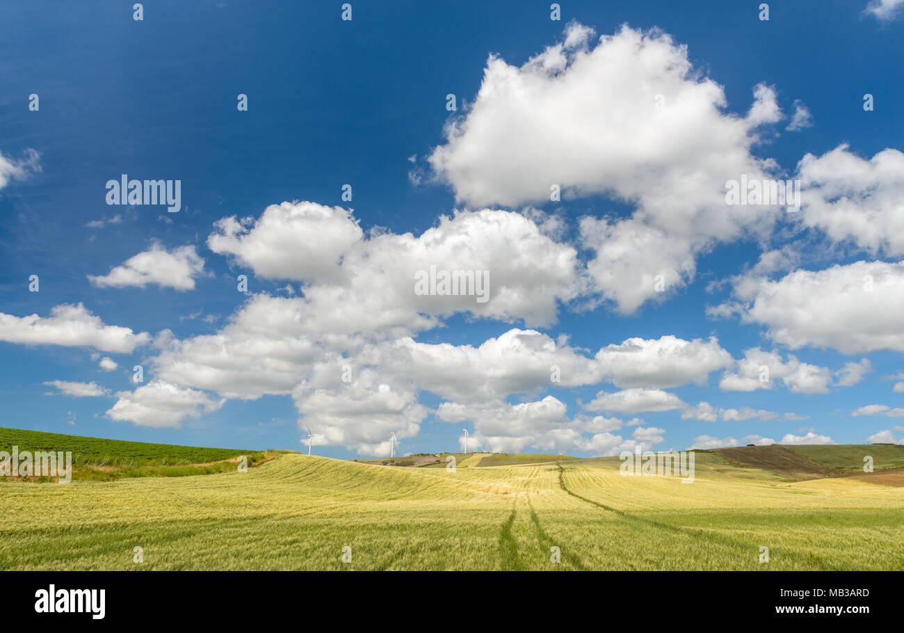 Fluffy Cumulus clouds against an azure blue Mediterranean sky - Stock Image