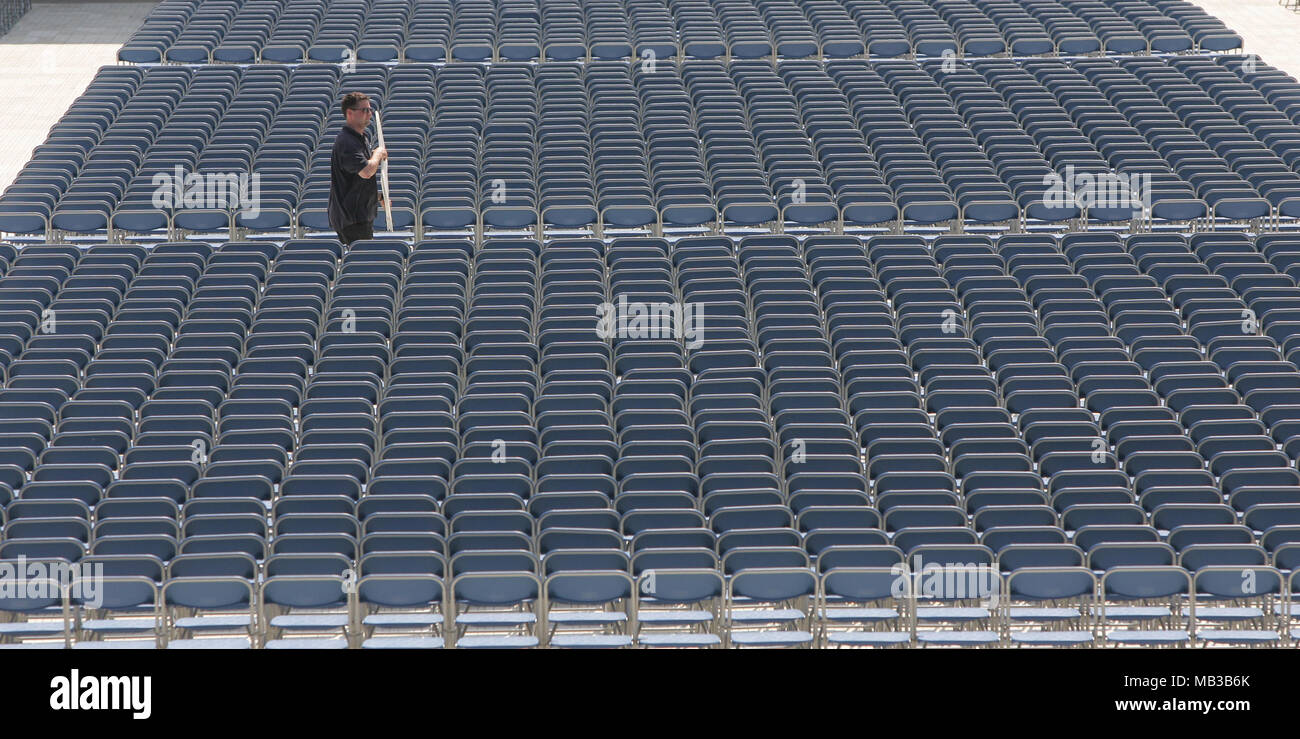 A single man lays out hundreds of rows of plastic temporary blue seats before concert. - Stock Image