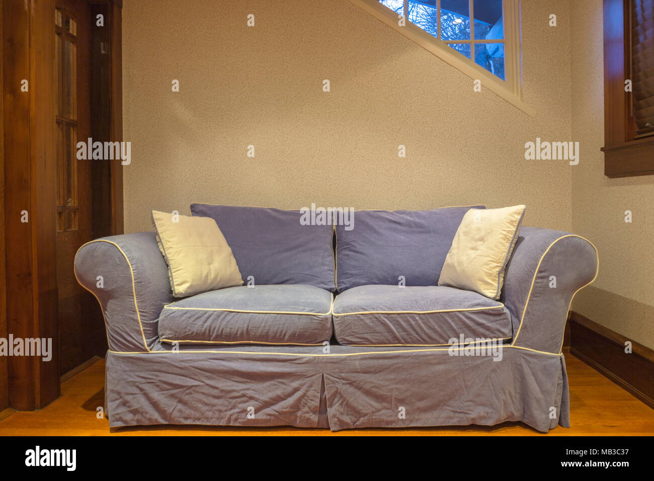 BLUE COUCH ON OAK WOODEN LIVING ROOM FLOOR - Stock Image