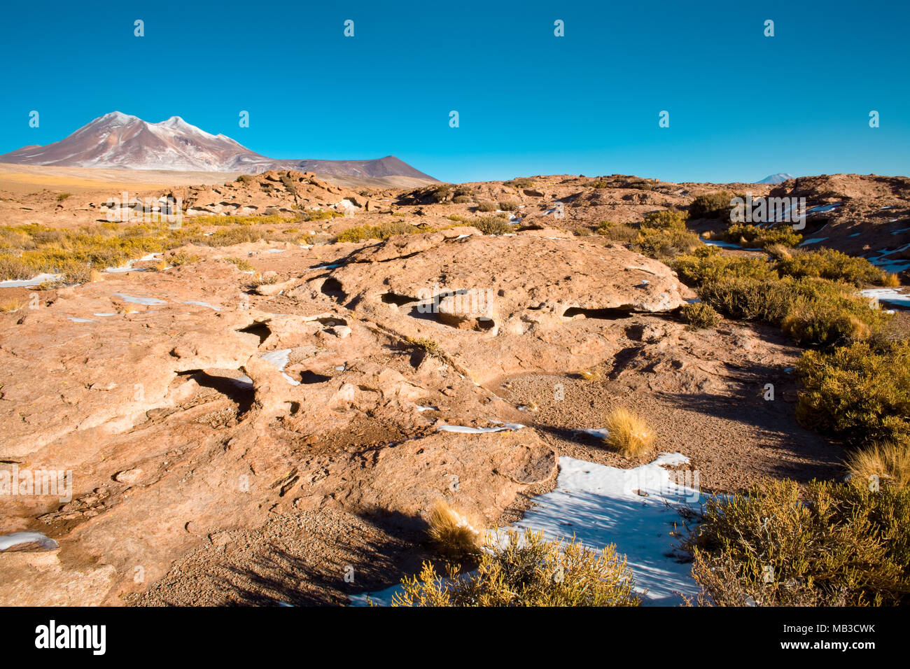Rock formations of dry lava, with Cerro Miniques (Miniques hill) in the background in the Altiplano (high Andean Plateau), Los Flamencos National Rese - Stock Image