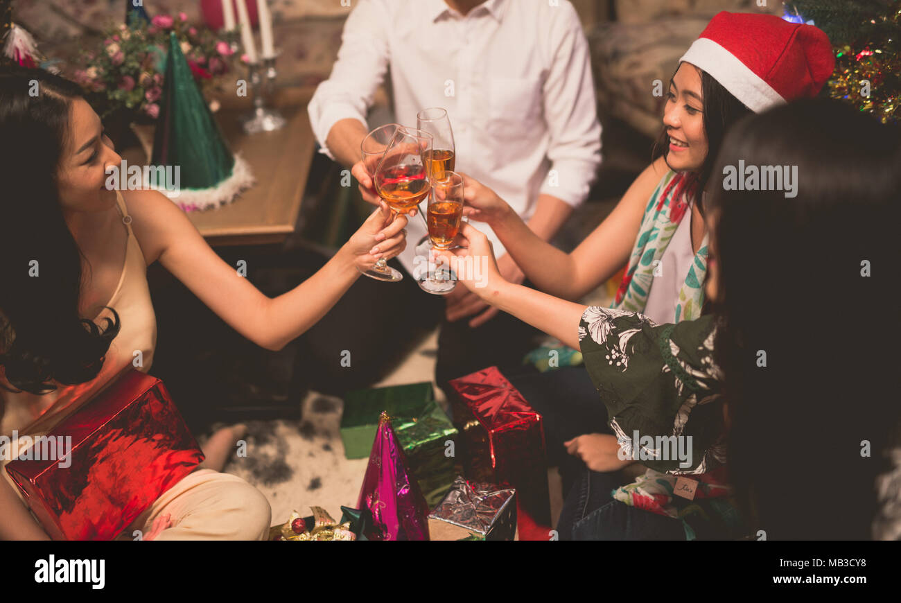 Group Of Friends Enjoying Christmas Drinks In Bar Celebrating x mas at home. clink glasses - Stock Image