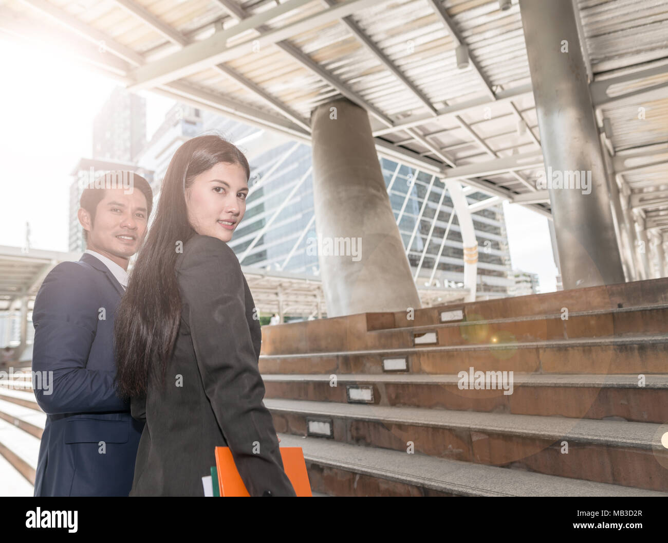 Portrait of smart confident business man boss and colleague business woman looking and smiling at camera, financial city outdoors. Elegant professiona - Stock Image