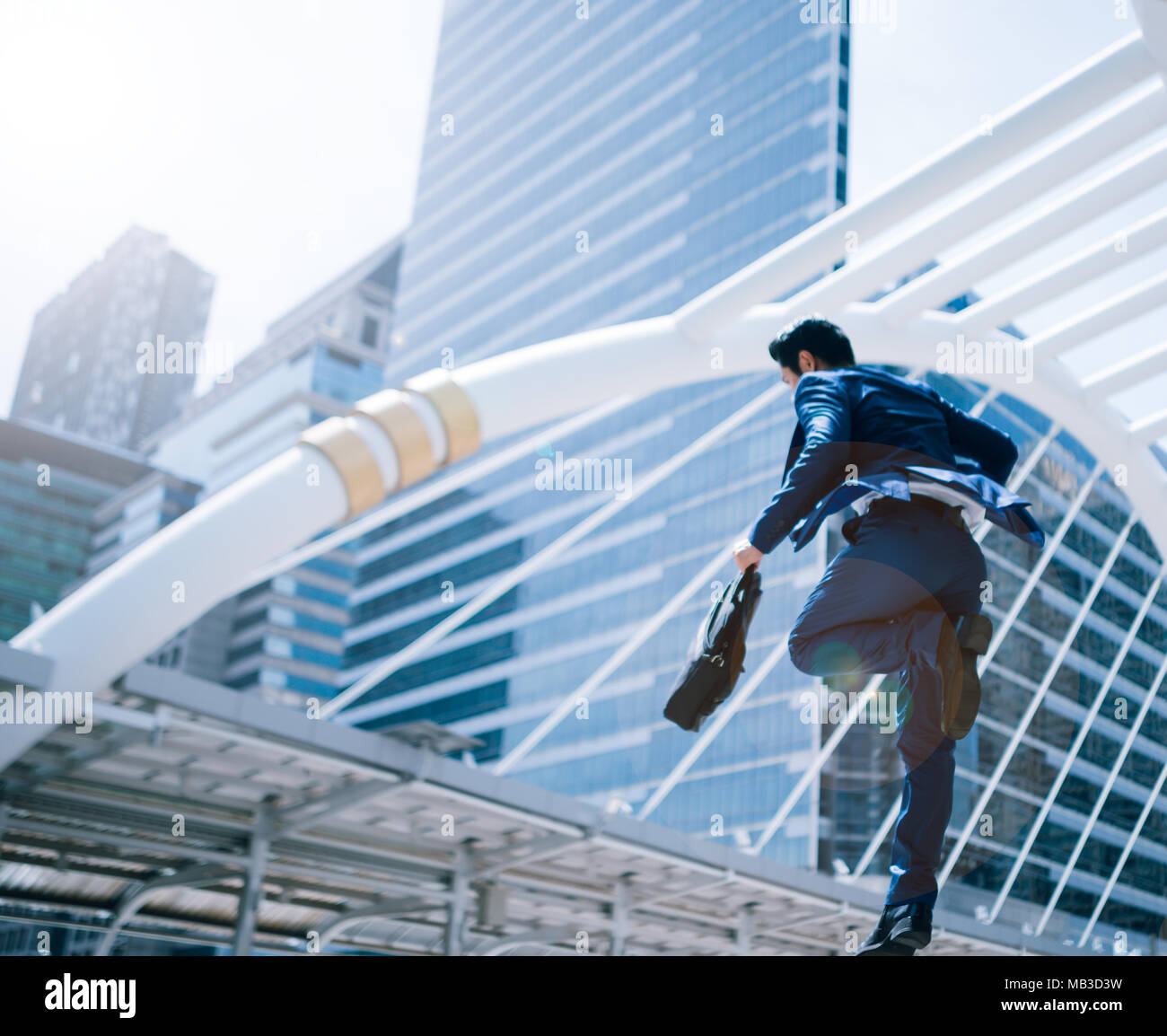 jumping running business man in front of buildings stock photo