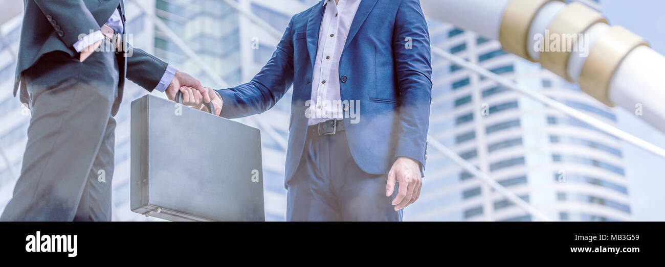 Businessman transfer deal, business black briefcase exchange urban city background.handover of a suitcase in the hands of partners. - Stock Image