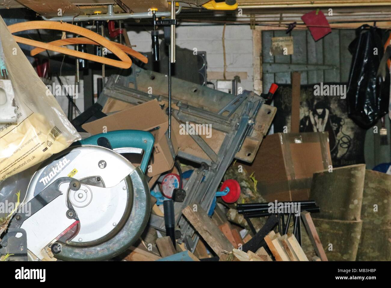 Very cluttered garage filled with wood, power tools, tools, work bench, child bike, and general rubbish - Stock Image
