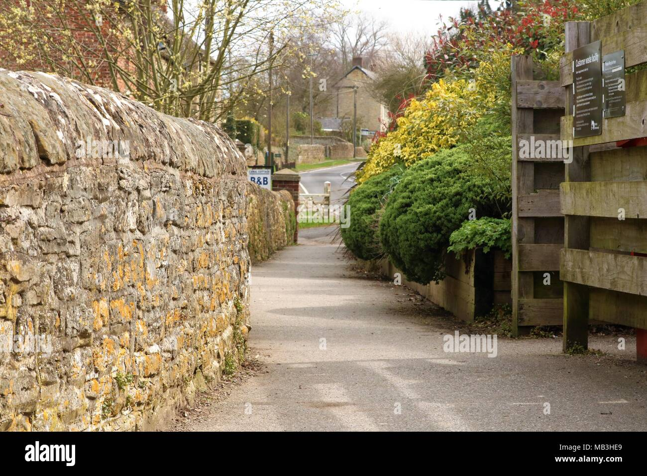 English quaint idyllic village walk in Oxfordshire, UK with stone wall, trees and view of road in the distance - Stock Image