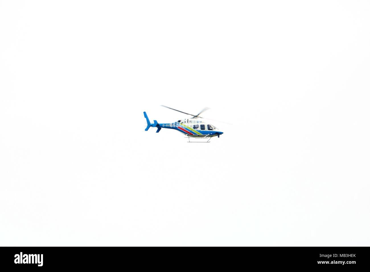 G-Ride National Grid helicopter in flight against a white cloudy sky - Stock Image