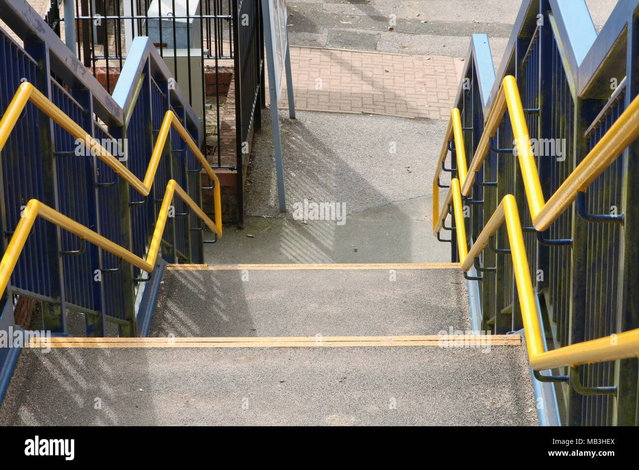 View looking down concrete steps with yellow handrails - Stock Image