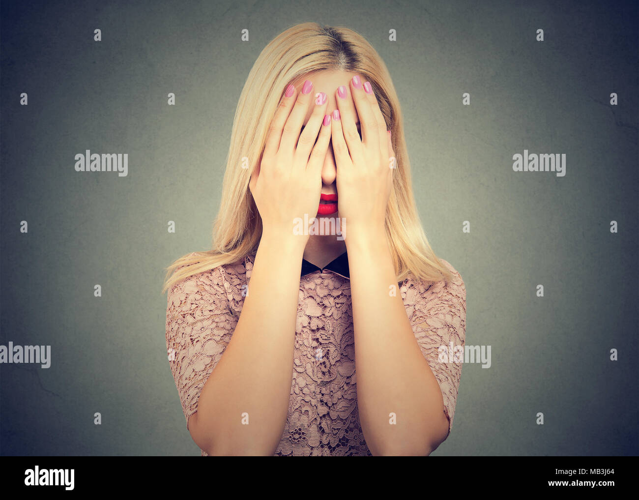 Anonymous blond girl hiding eyes while covering them with hands standing on gray background. - Stock Image