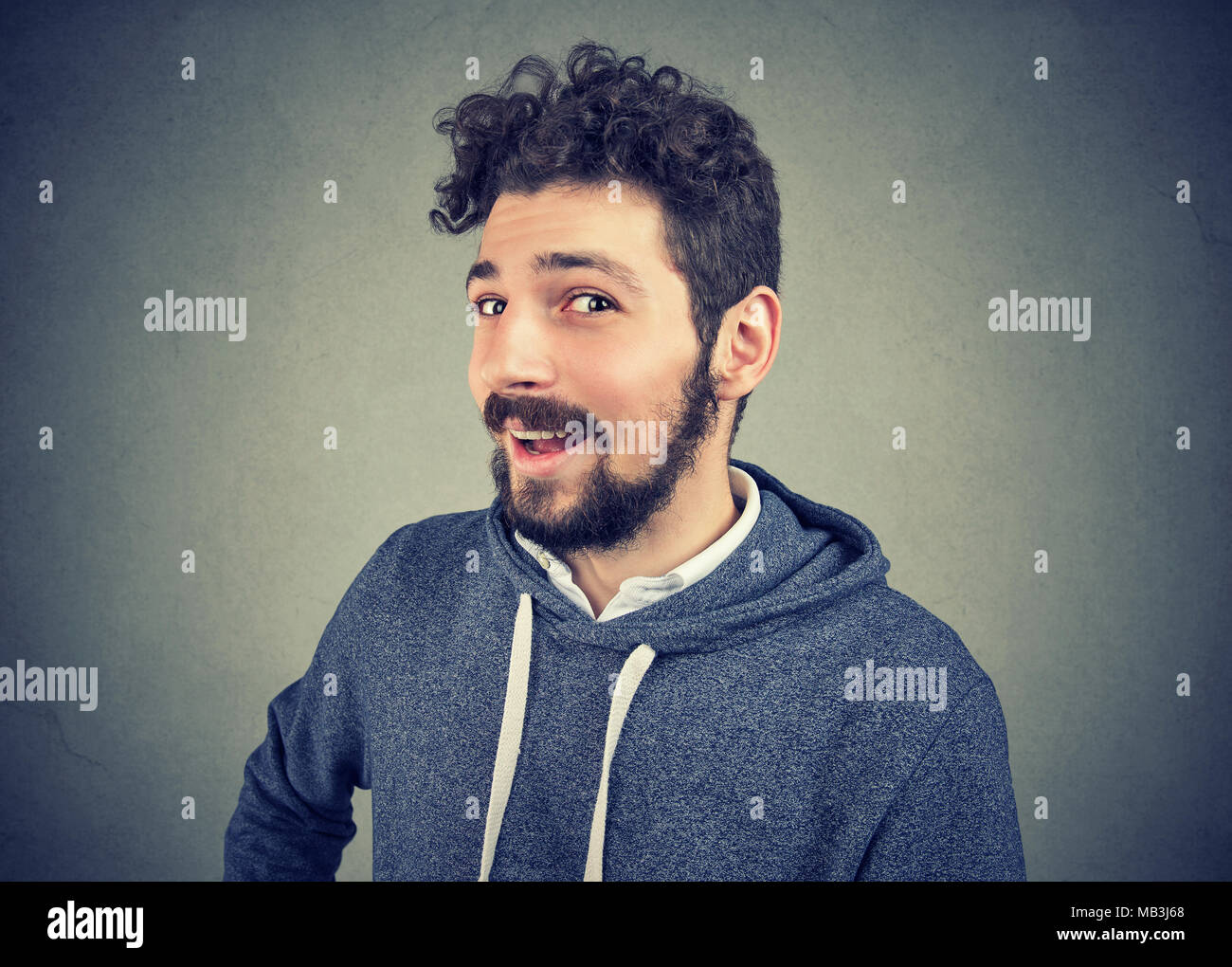 Cunning tricky young man looking with smile at camera - Stock Image