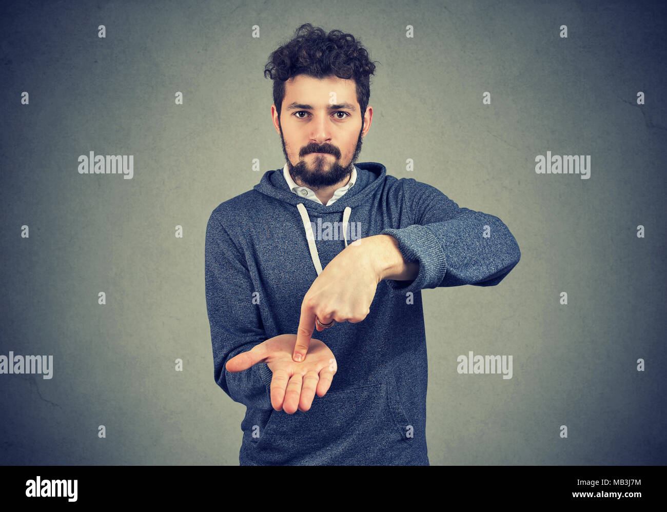 Young serious hipster man asking for more money to pay back debt - Stock Image