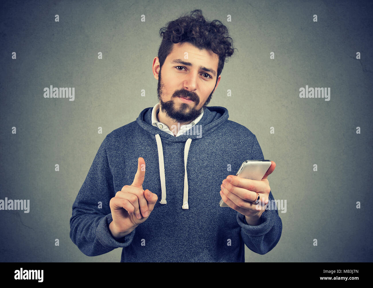 Young man with smartphone. Handsome guy holding cell phone showing no, don't, attention with finger hand gesture. Blocking forbidden adult contents co - Stock Image