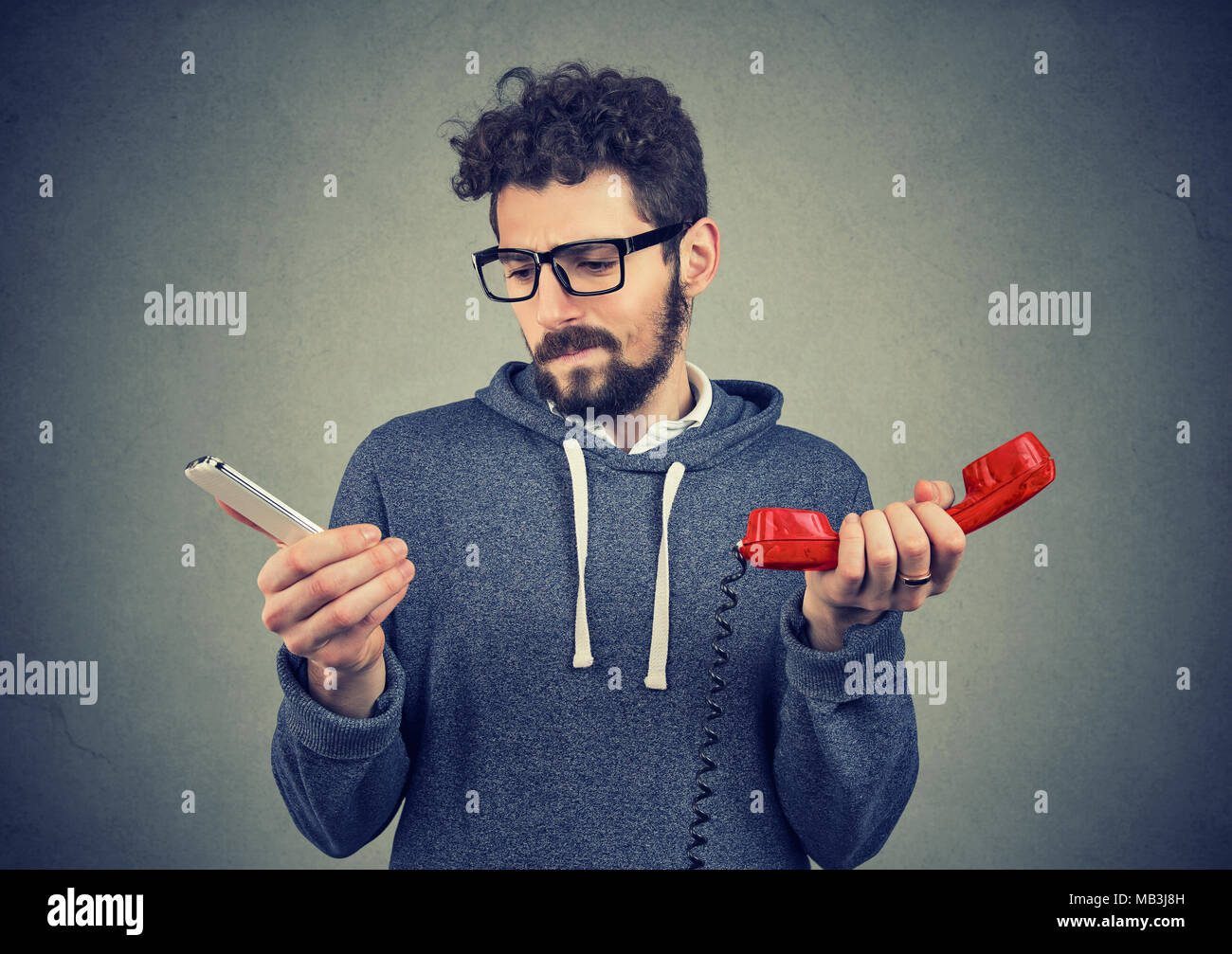 Young hipster man looking puzzled about old fashioned and contemporary gadgets. - Stock Image