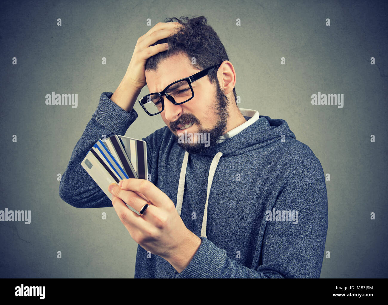 Confused stressed man looking at too many credit cards full of debt - Stock Image