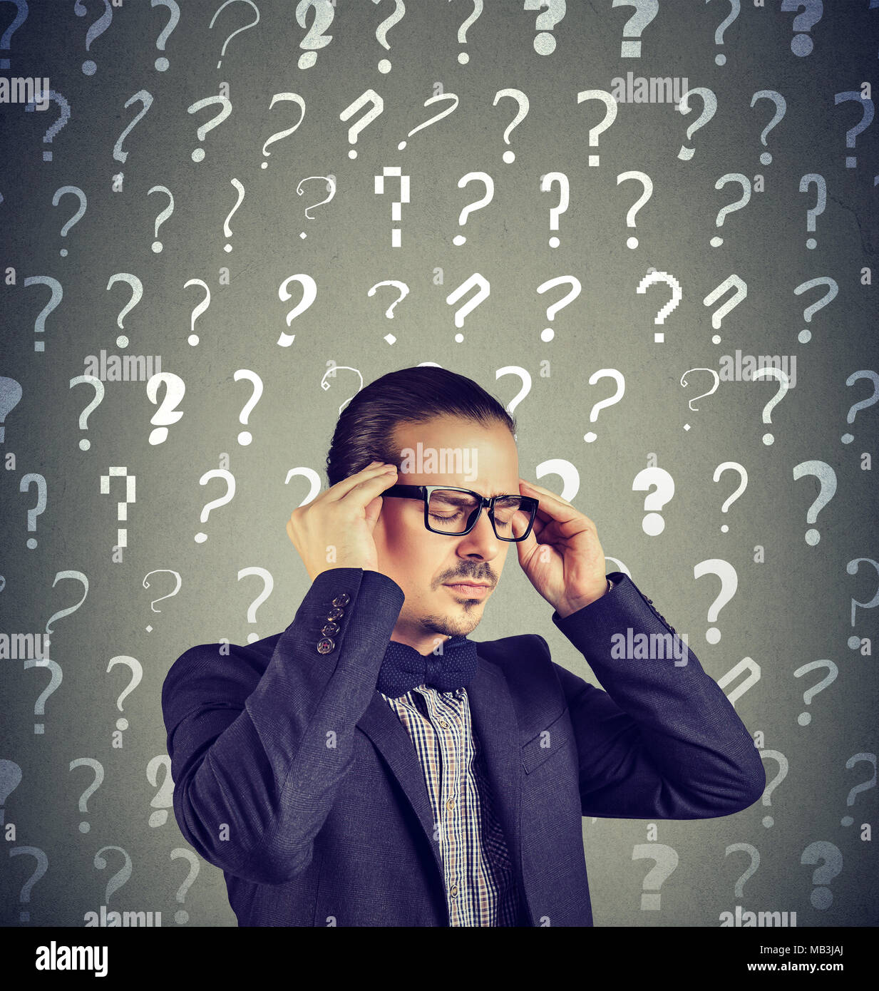 Stressed overburdened young man has too many questions and no answer - Stock Image