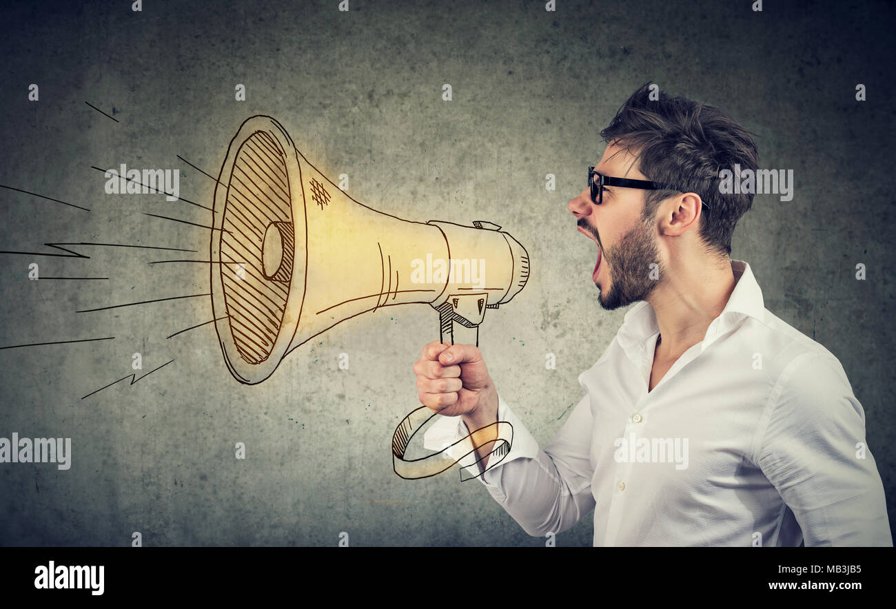 Side view of man in eyeglasses and white shirt spreading news and making announcement with loudspeaker. - Stock Image