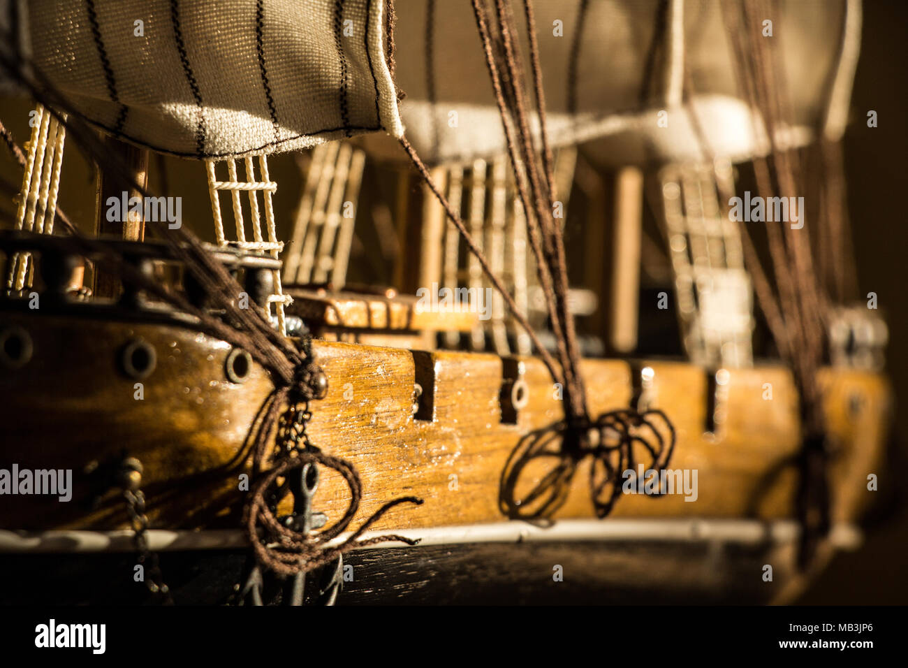 Horizontal close up shot of a model wooden sail ship - Stock Image