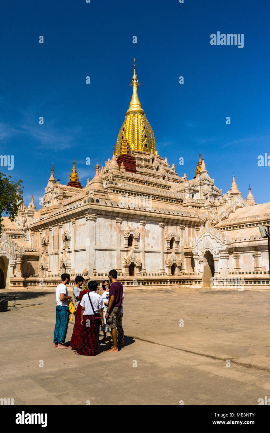 Ananda Temple vertical photo, Burmese tour guide with western tourists in foreground, in Bagan Myanmar - Stock Image