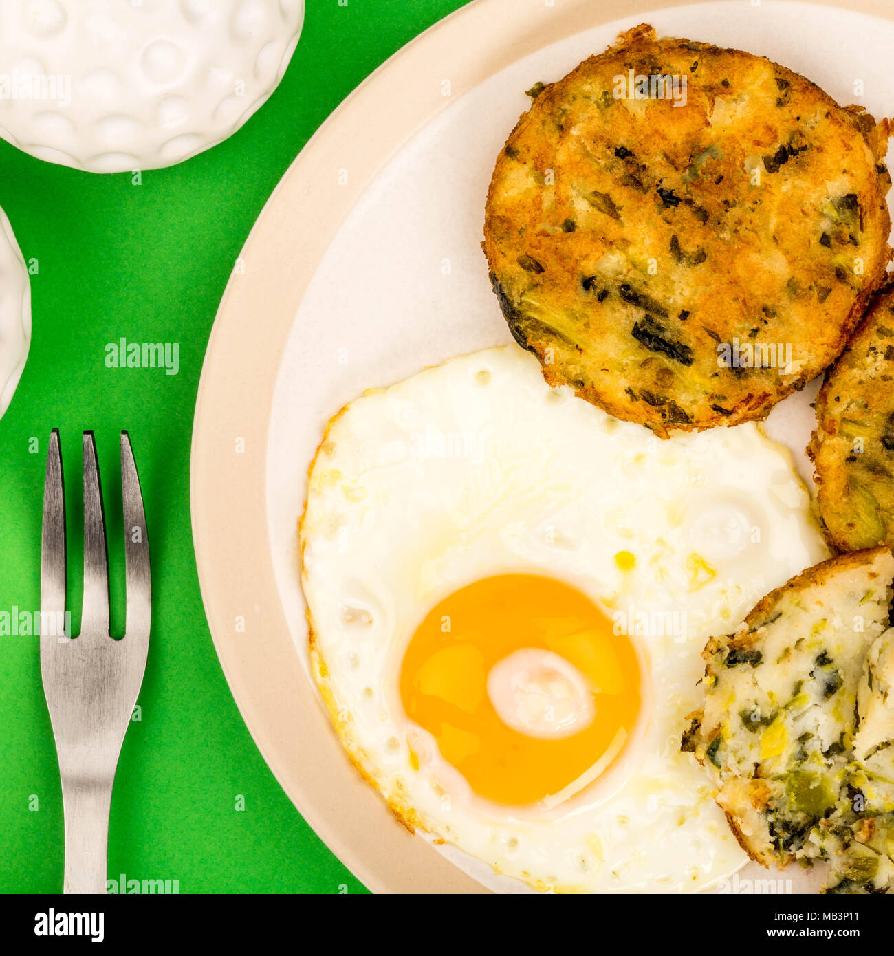 Cooked Vegetarian Bubble And Squeak Cakes With A Fried Egg Against A Green Background - Stock Image