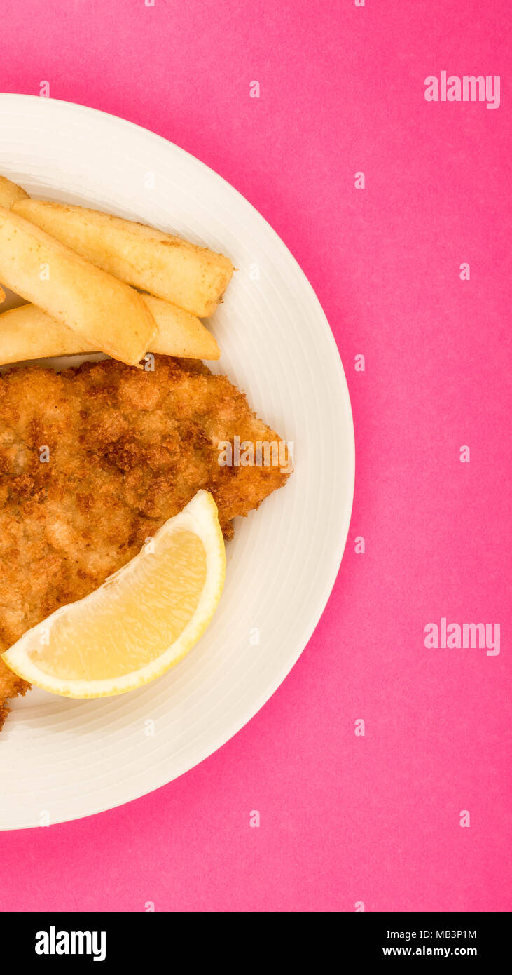 Traditional Popular Fish And Chips Against A Pink Backgound With A Slice Of Lemon - Stock Image