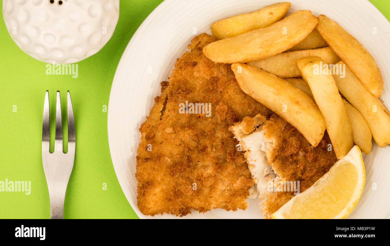 Traditional Popular Fish And Chips Against A Green Background And A Slice Of Lemon Stock Photo