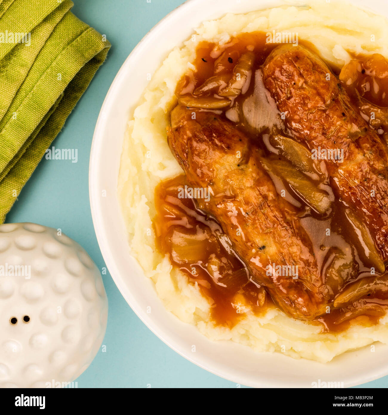 Sausage And Mashed Potatoes With Onion Gravy Against A Blue Background - Stock Image