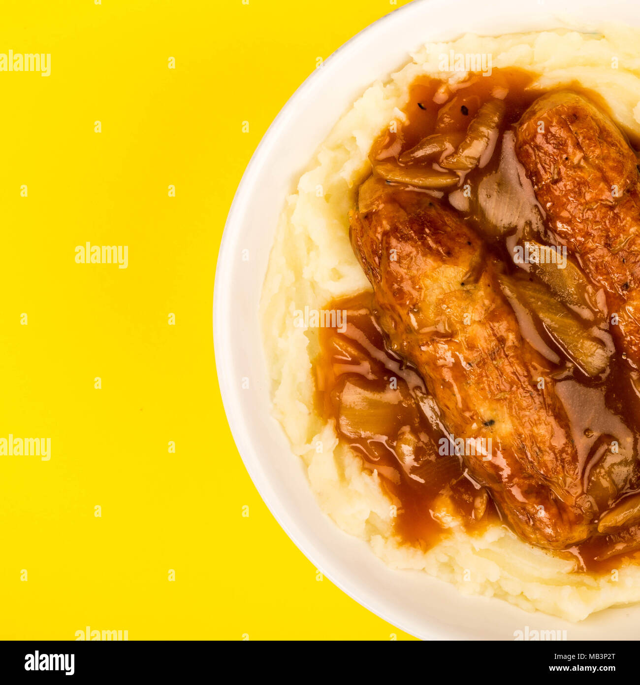 Sausage And Mashed Potatoes With Onion Gravy Against A Yellow Background - Stock Image