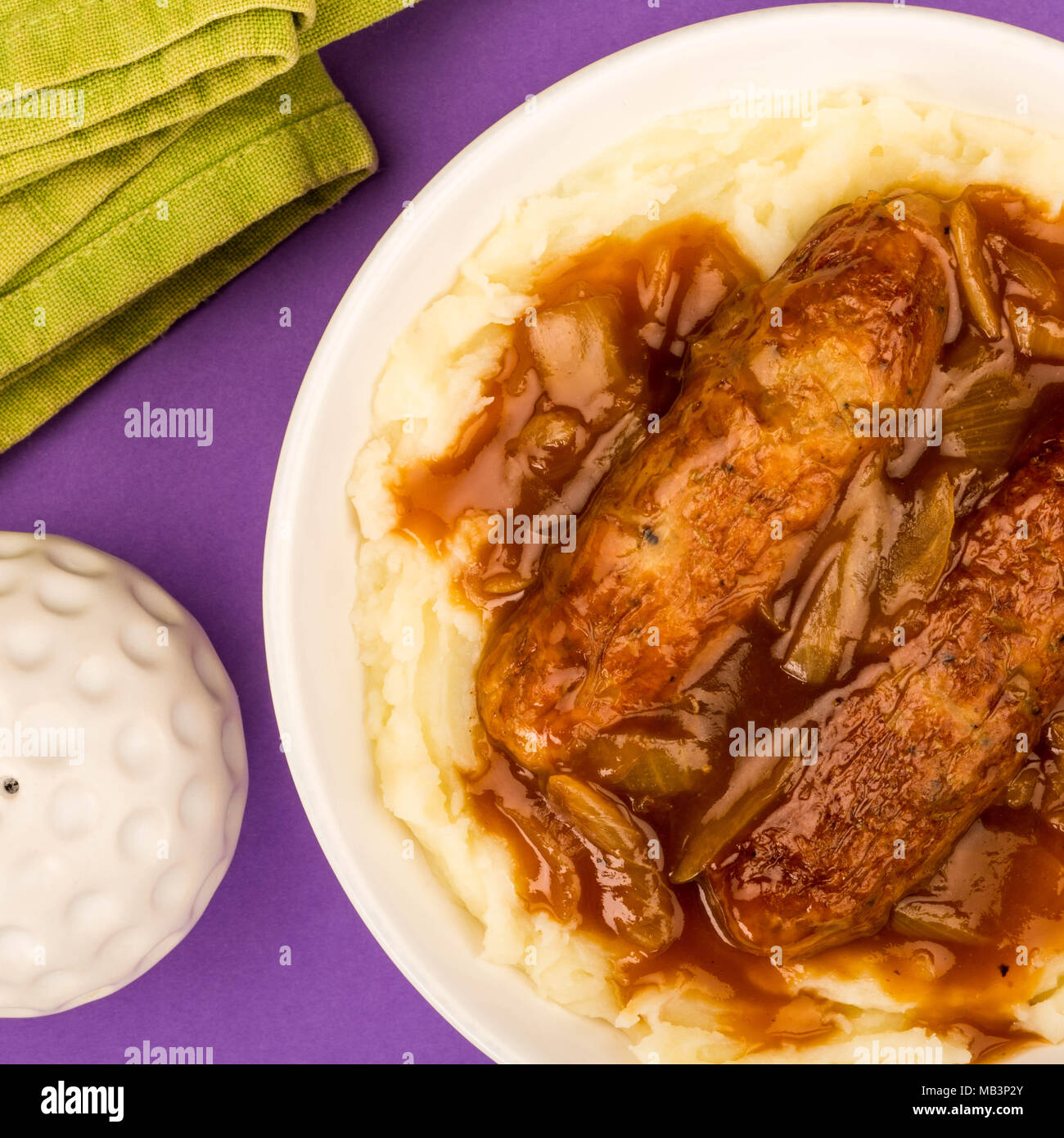 Sausage And Mashed Potatoes With Onion Gravy Against A Purple Background - Stock Image