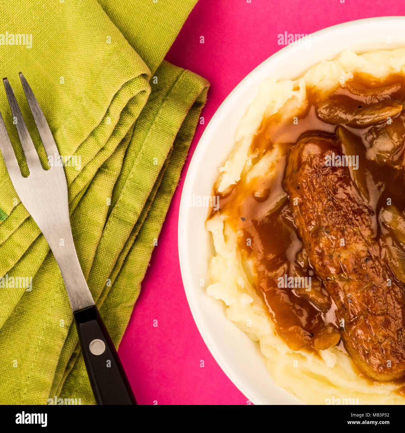 Sausage And Mashed Potatoes With Onion Gravy Against A Pink Background - Stock Image