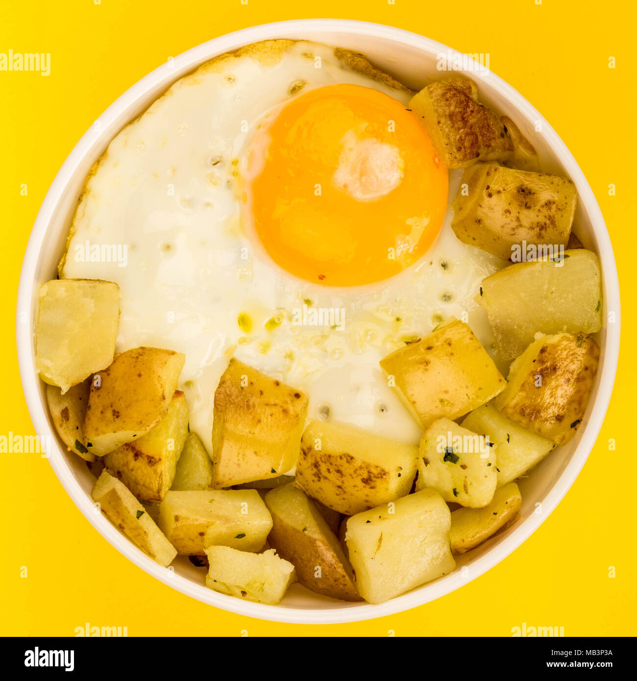 Fried Egg With Fried Potatoes Breakfast In A Bowl Against A Yellow Background - Stock Image