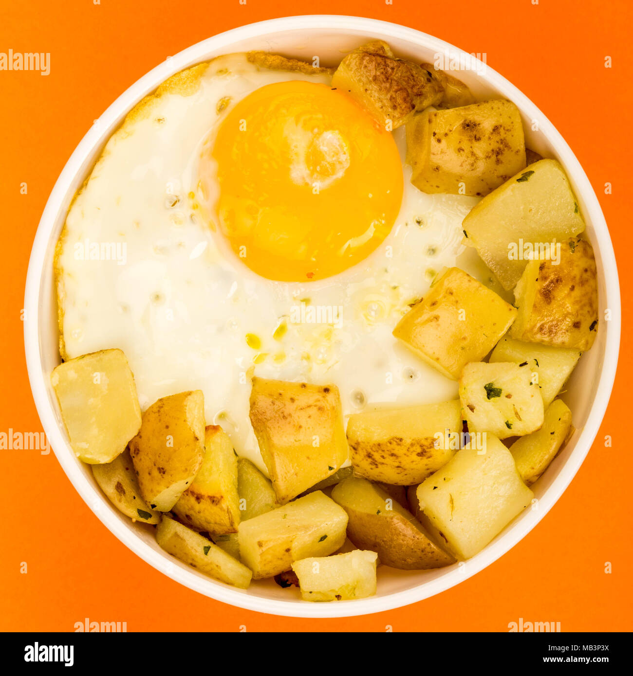 Fried Egg With Fried Potatoes Breakfast In A Bowl Against An Orange Background - Stock Image