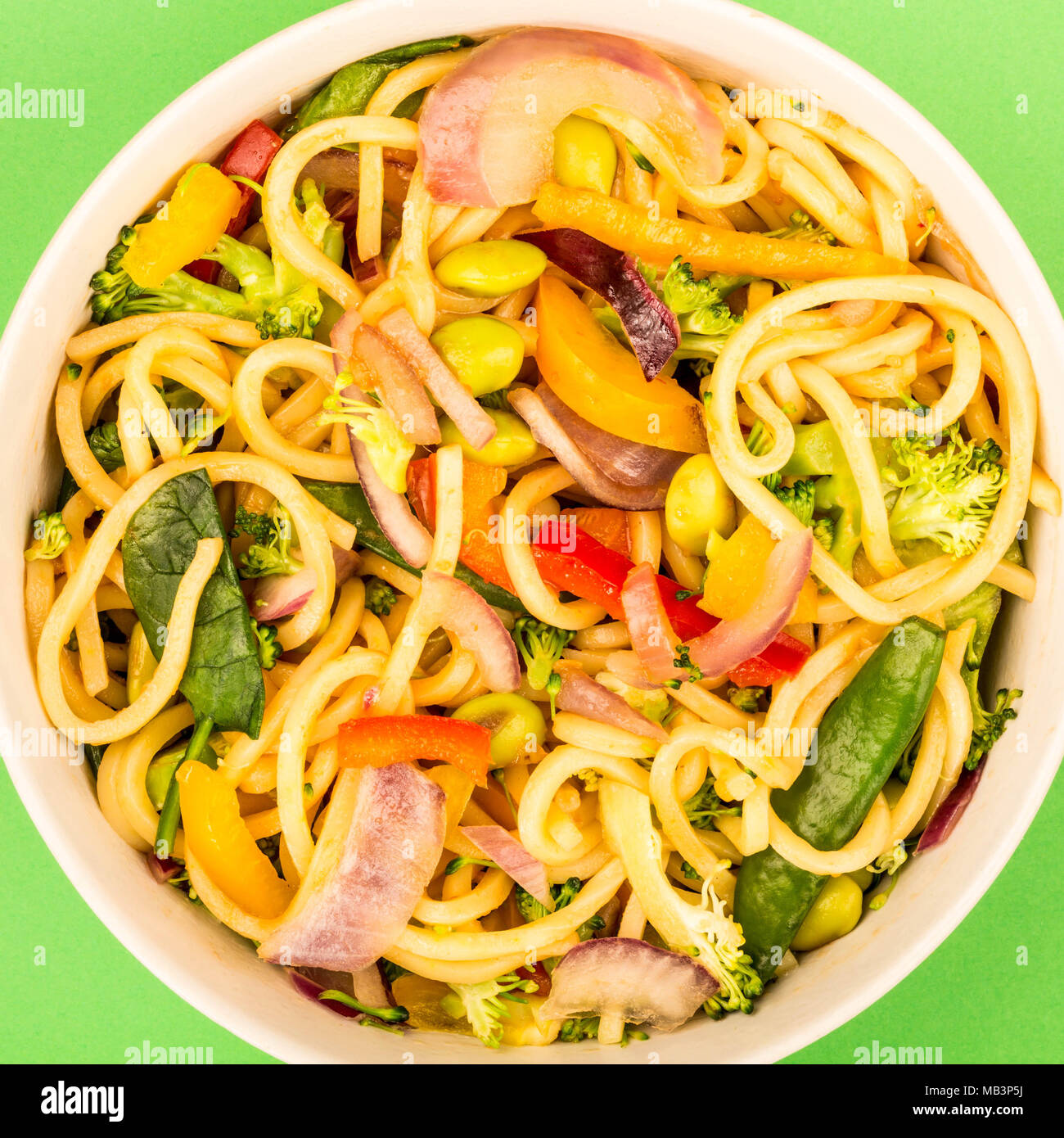 Stir Fried Egg Noodles With Fresh Vegetables Against A Green Background - Stock Image