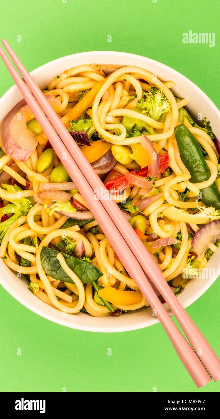 Stir Fried Egg Noodles With Fresh Vegetables Against A Green Background - Stock Image