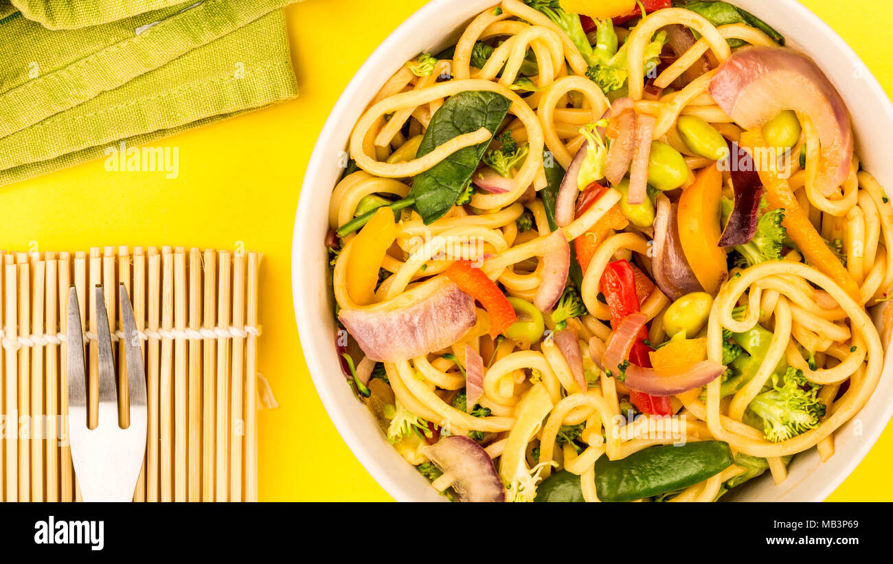 Stir Fried Egg Noodles With Fresh Vegetables Against A Yellow Background - Stock Image