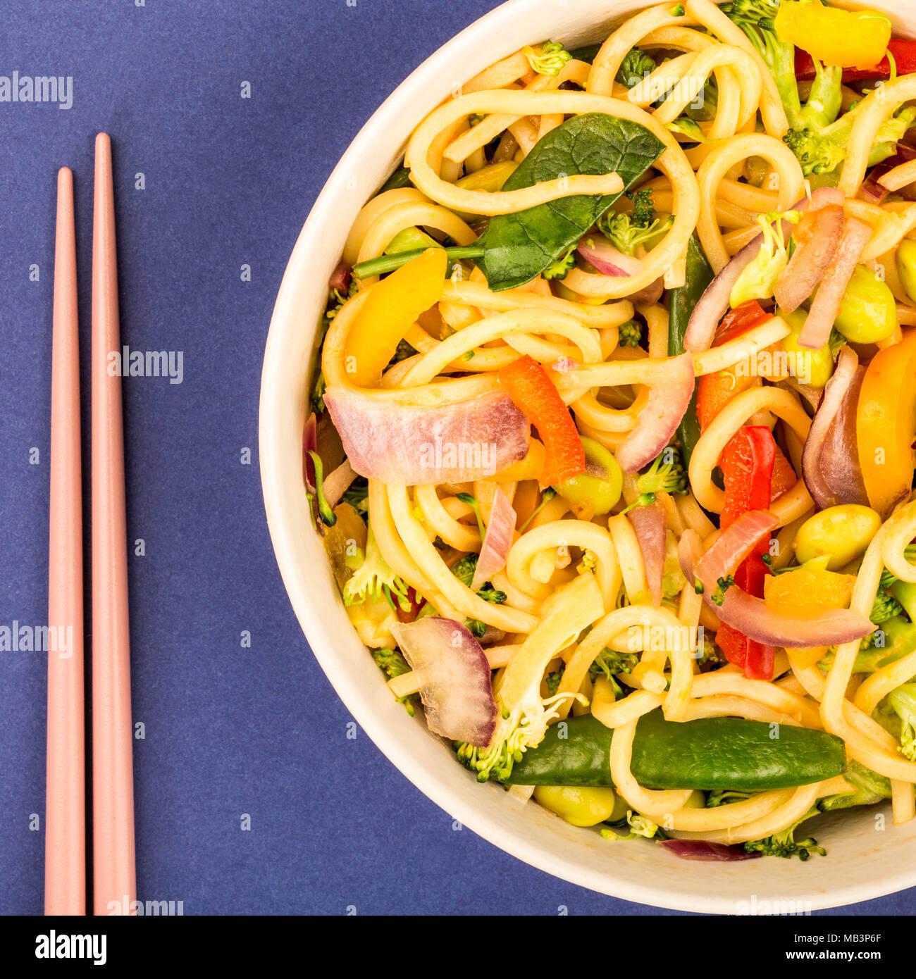 Stir Fried Egg Noodles With Fresh Vegetables Against A Purple Background - Stock Image