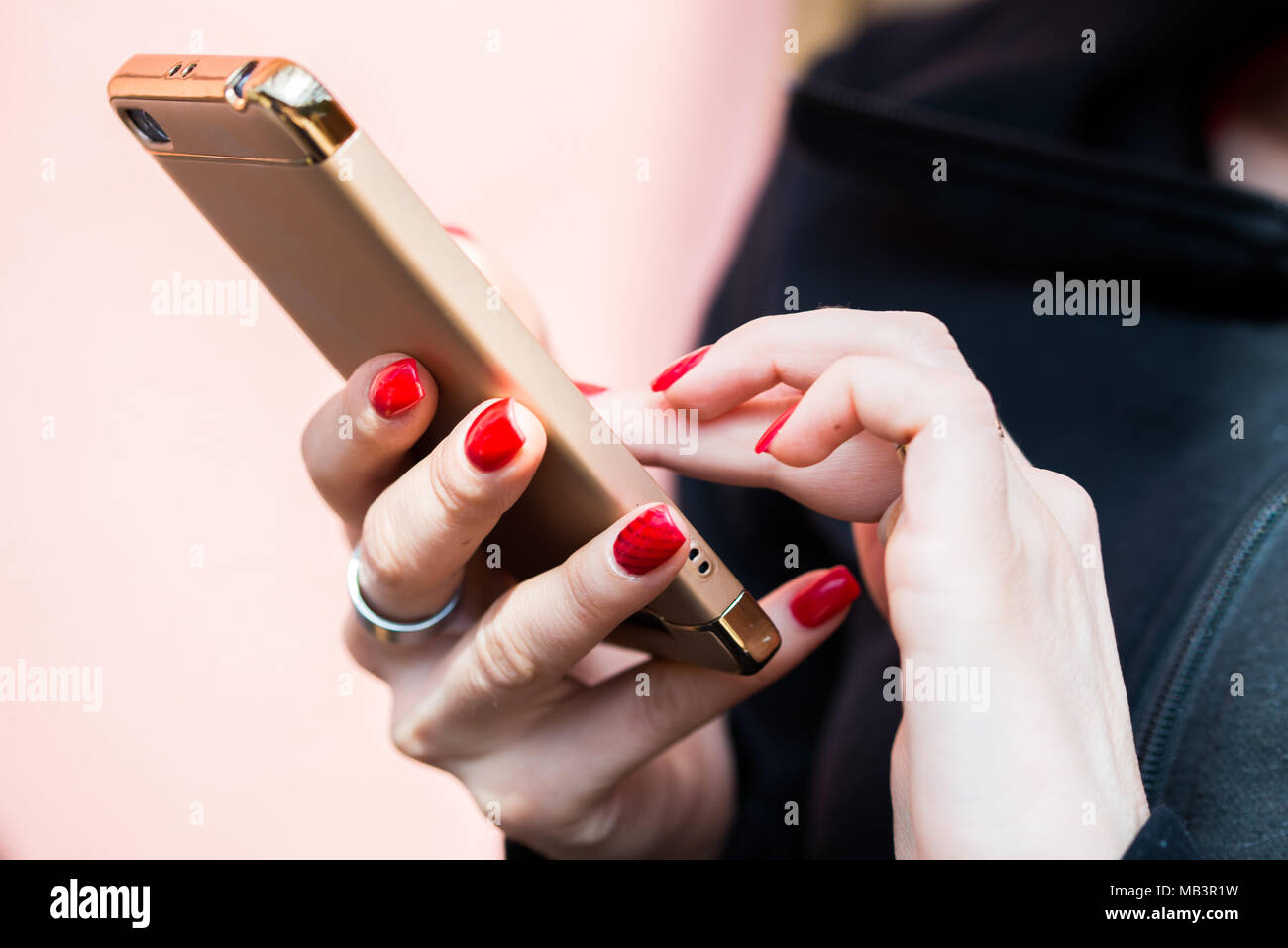 Female hands texting on smartphone, nicely manicured fingernails - Stock Image