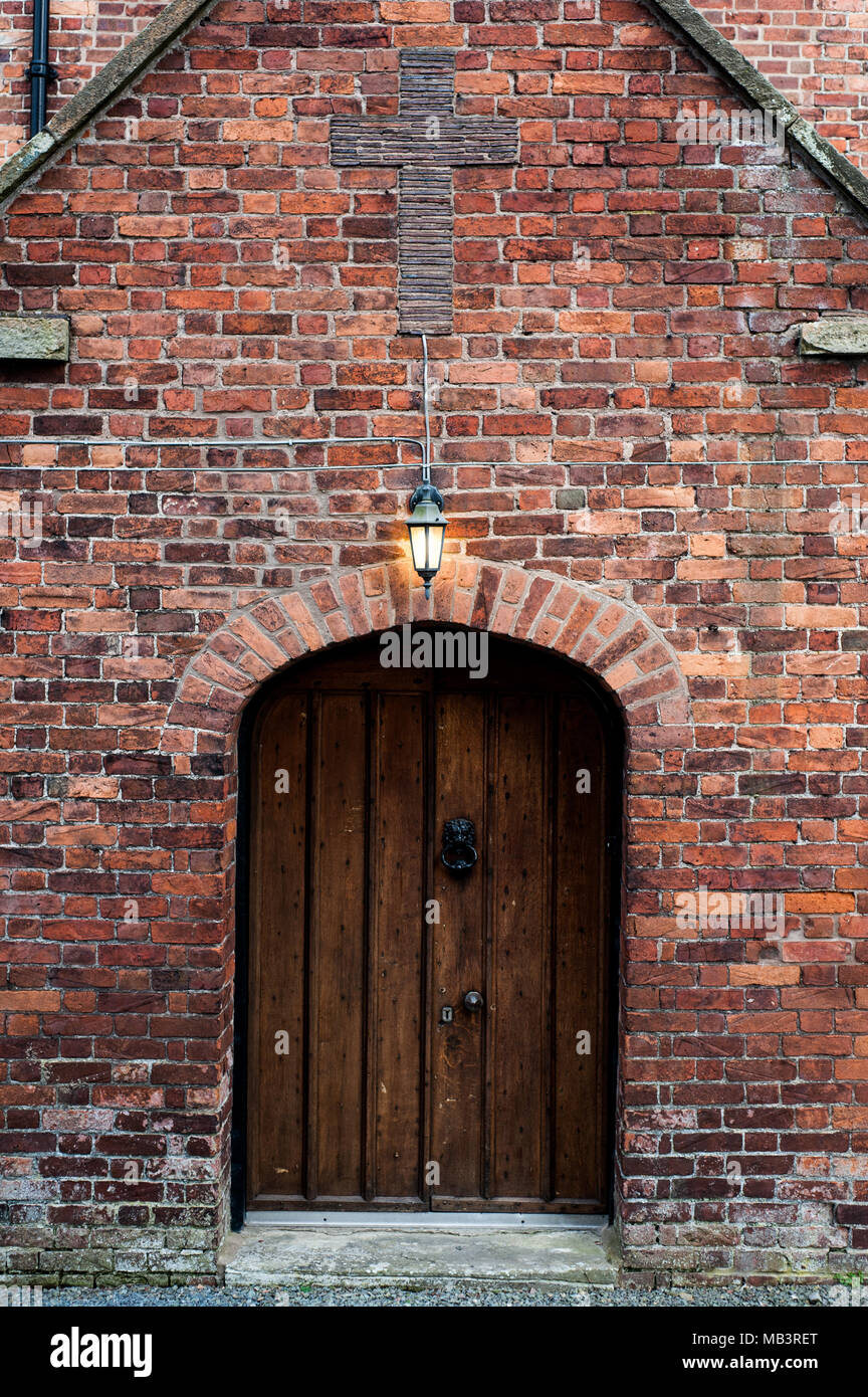 Old wooden Rectory door with Christian cross above door at 11th century St Eata's church vicarage in Atcham, Shropshire, England - Stock Image