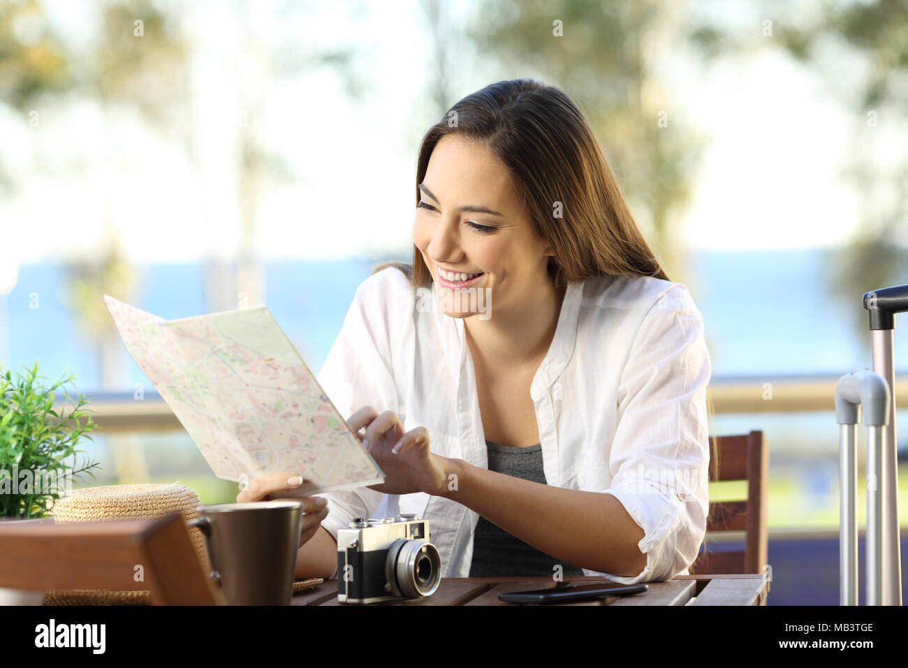Happy tourist planning vacations consulting a guide in an apartment balcony - Stock Image