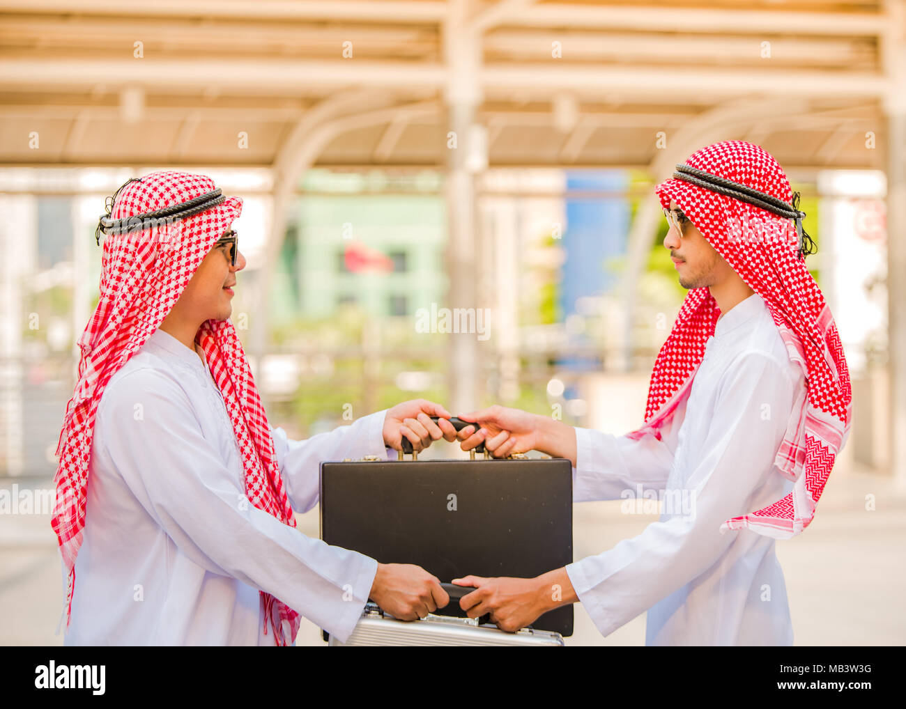 Successful Arabic business people shaking hands exchange bag over a deal - Stock Image