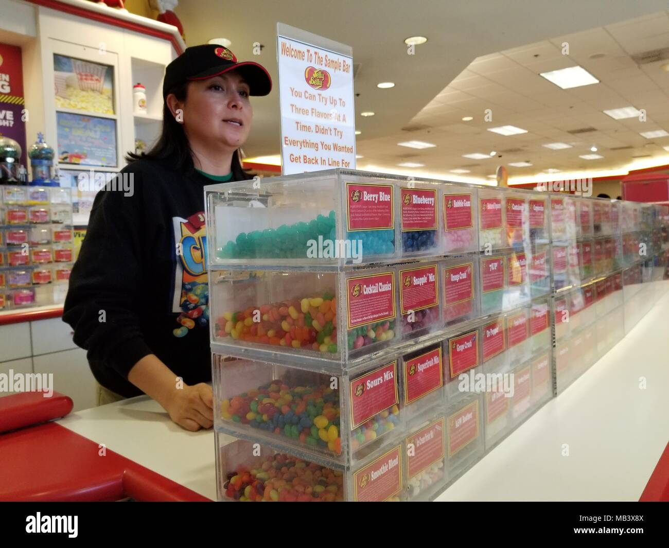 A staff member stands behind the Tasting Bar at the Jelly Belly jelly bean candy factory in Fairfield, California, and offers free samples of every confection made by the company, March 27, 2018. () - Stock Image