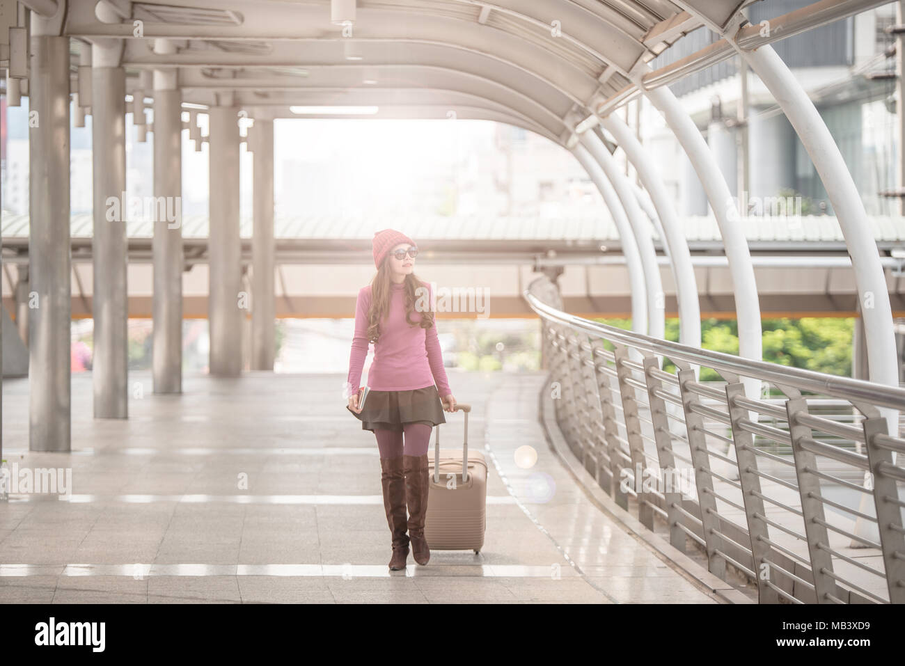 Portrait of a traveling young woman with luggage walking through the poles lined of international airport terminal Stock Photo