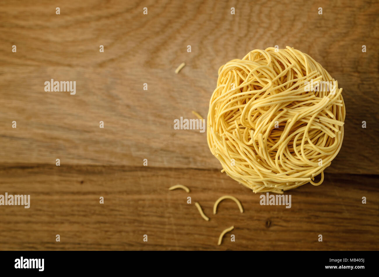 Overhead shot of stacked egg noodle nests with broken fragments scattered on oak wood surface below. Copy space to left. - Stock Image