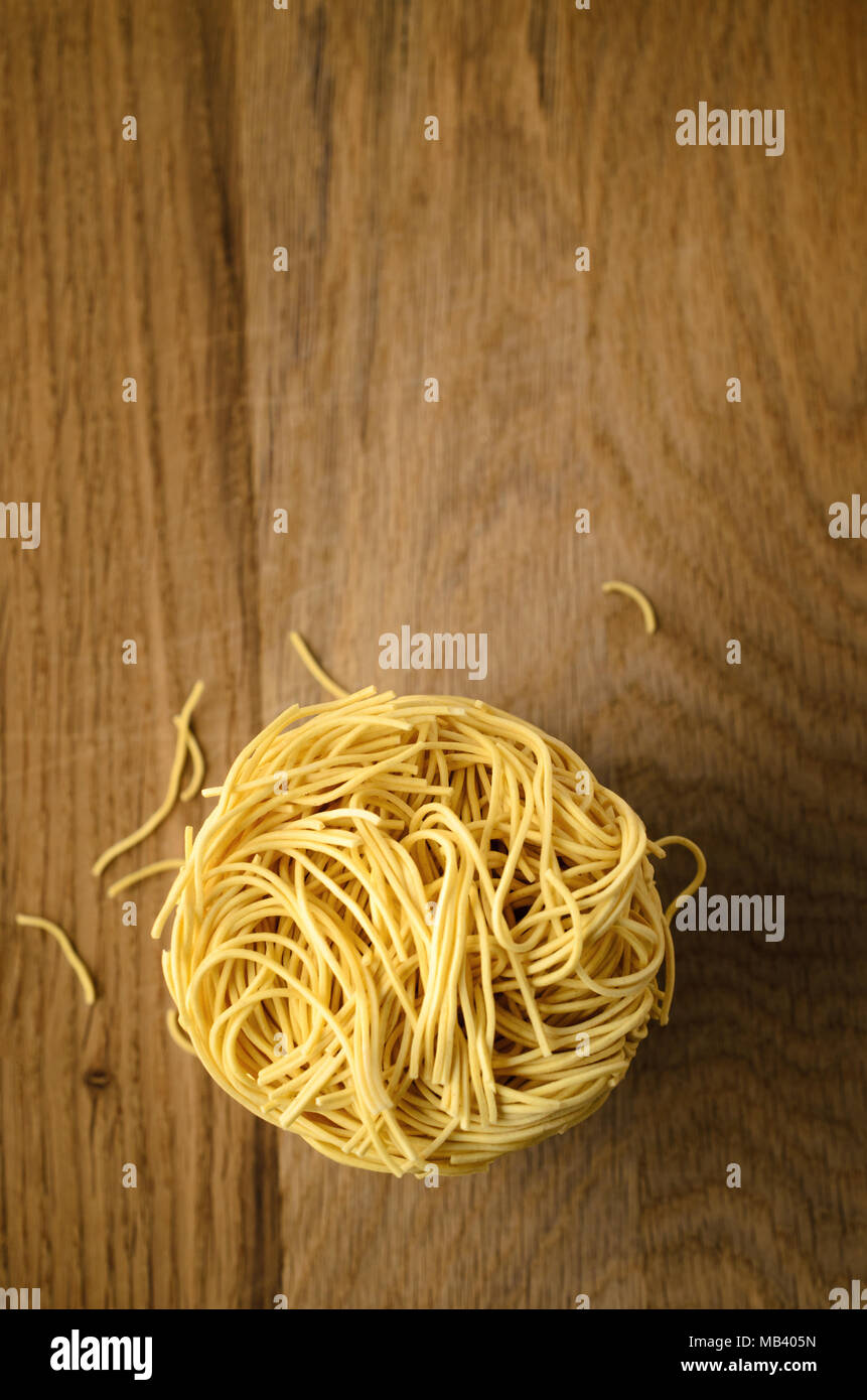 Overhead shot of egg noodles nest stack on wooden surface with broken noodle fragments scattered below. Copy space above. - Stock Image
