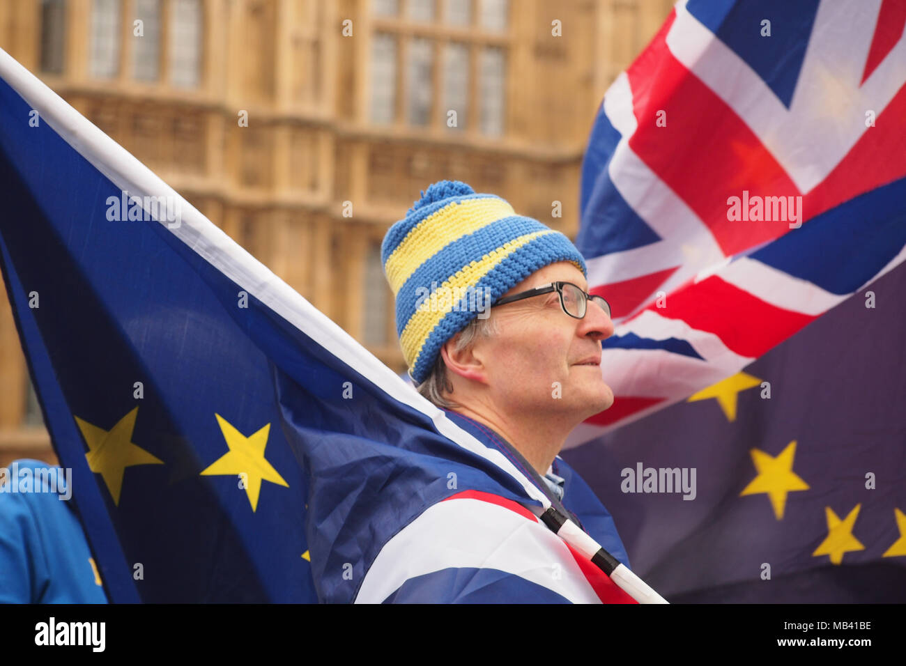 A man outside the Houses of Parliament, London protesting against Brexit with the European and Union flags - Stock Image