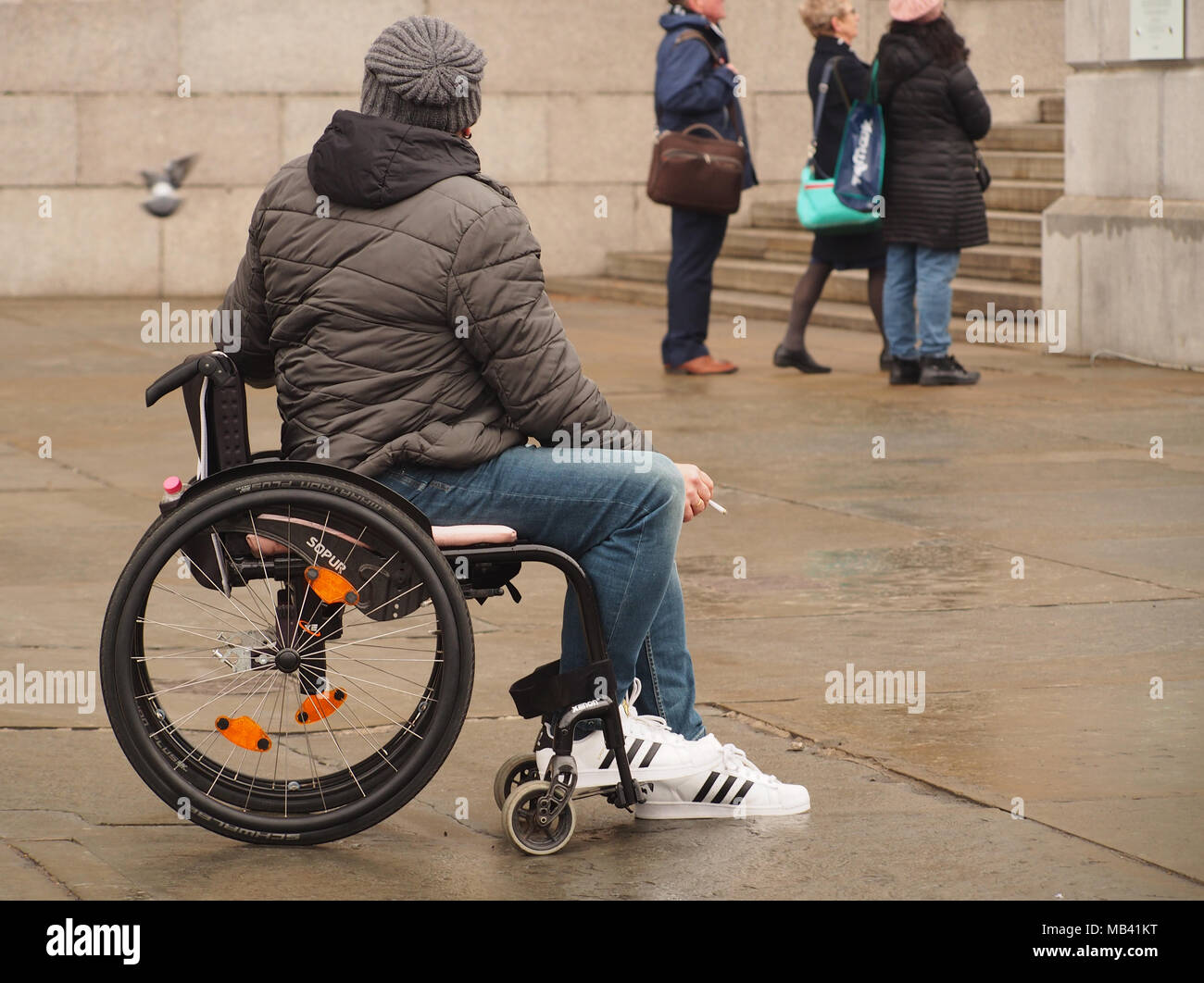 A young man in a wheelchair in Trafalgar Square, London seemingly on his own watching the sights around him - Stock Image