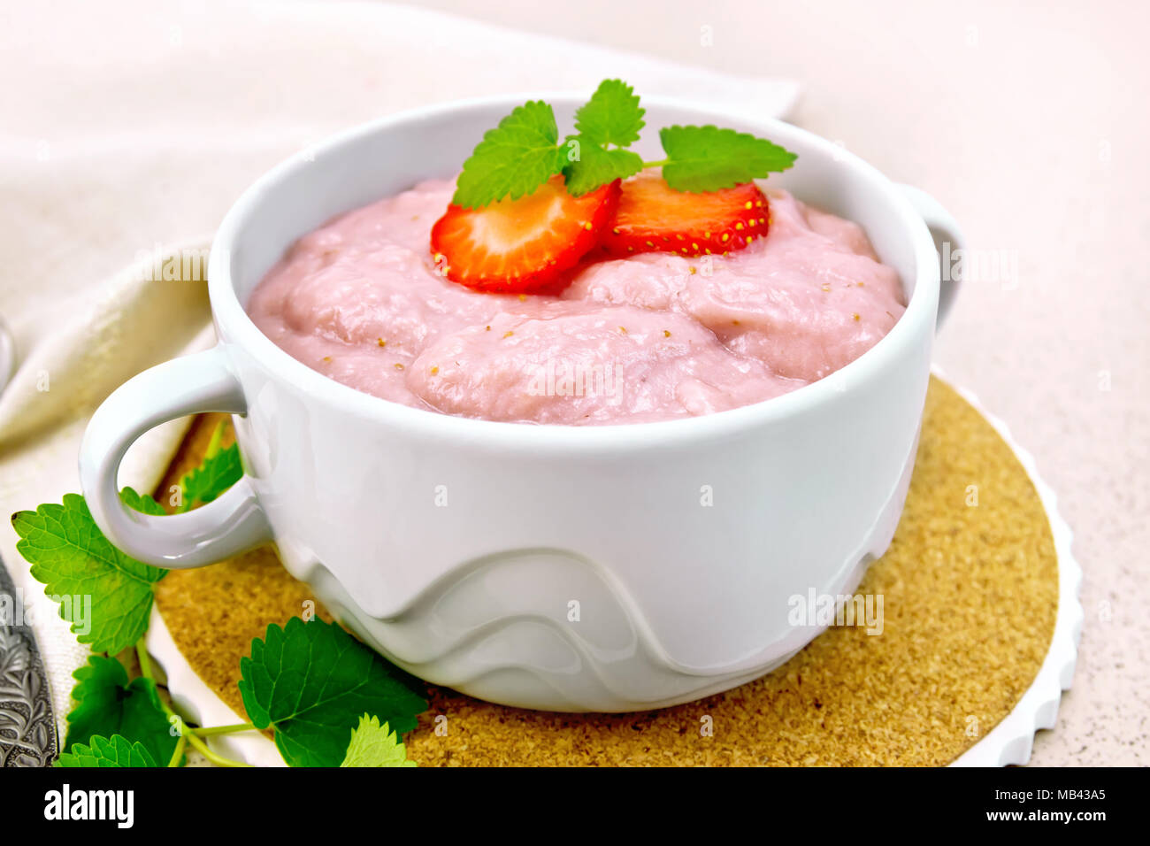 Strawberry soup with berries and mint in a bowl on a stand, a napkin and a spoon on a background of a granite table - Stock Image