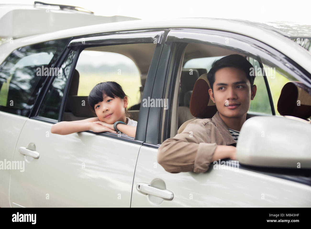 Happy little girl  with asian family sitting in the car for enjoying road trip and summer vacation in camper van - Stock Image