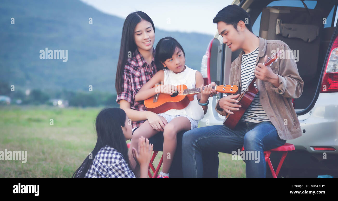 happy little girl playing ukulele with asian family sitting in the car for enjoying road trip and summer vacation - Stock Image
